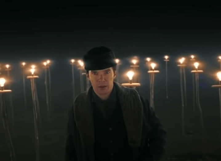 Benedict Cumberbatch as Thomas Edison standing in front of a series of lit lightbulbs.