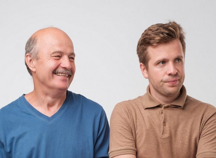 Dad in a blue jumper smiling beside his son in a brown shirt looking very unimpressed at his dad joke.