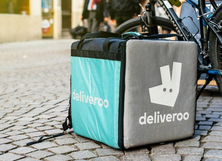 Deliveroo courier box on a cobbled street beside a delivery bike.