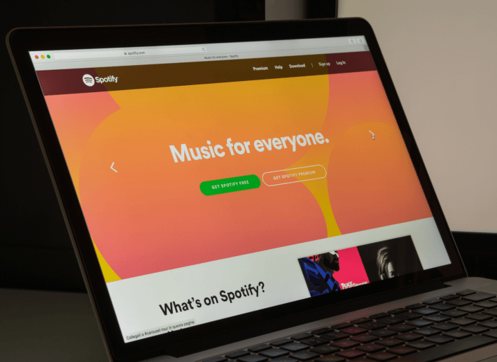 Spotify's orange homepage displayed on a laptop screen.