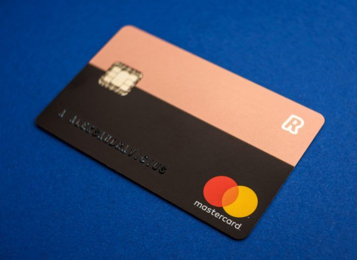 View of pink and black duochrome Revolut card on cobalt blue background.