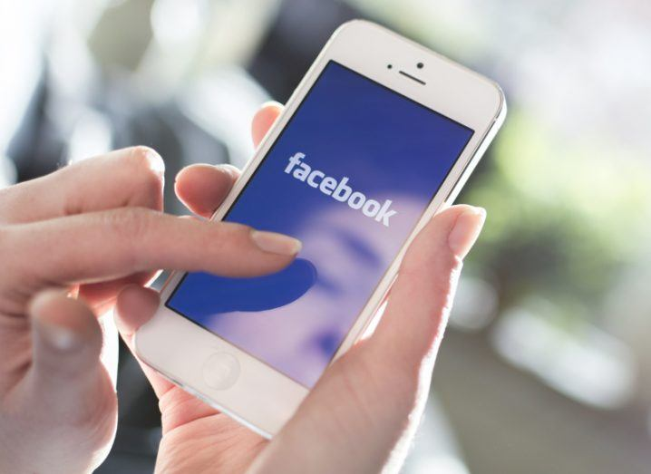 View of blue Facebook app loading screen on white smartphone's screen cradled by user's hand in brightly lit room.