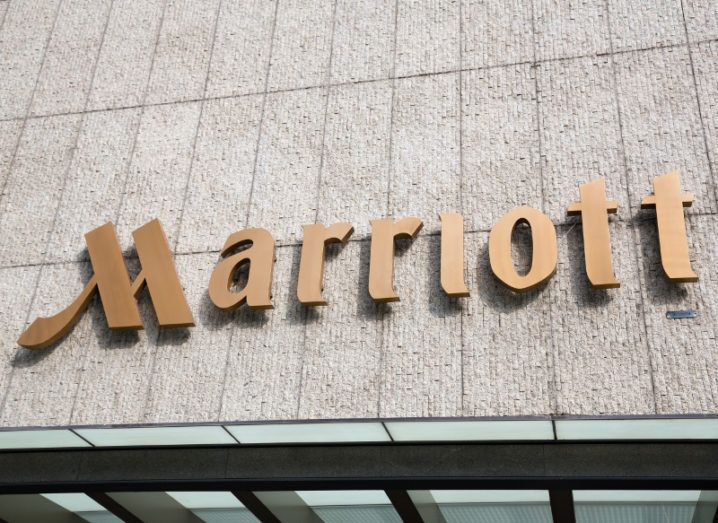 View of gold sign for Marriott hotel on grey slate tile facade of building.