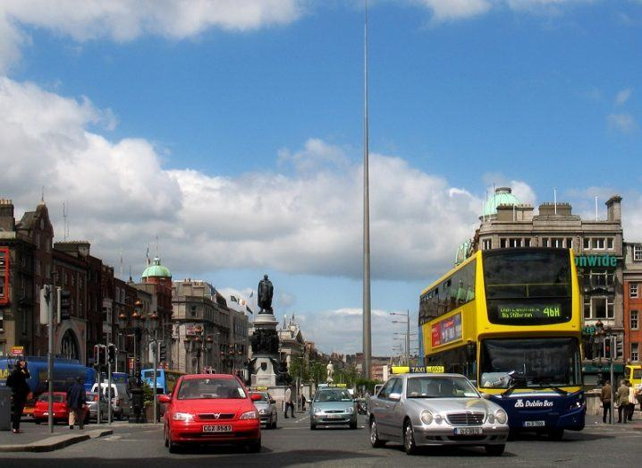 O'Connell Street Bridge and Street full of traffic looking towards the Spire against a blue sky with clouds.