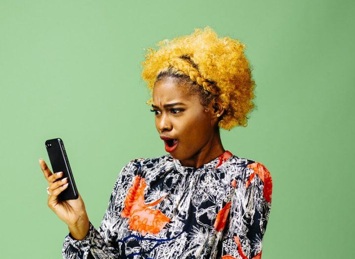Woman with yellow hair wearing a vibrant black, white and orange shirt making a shocked face while looking at a smartphone against a green backdrop.