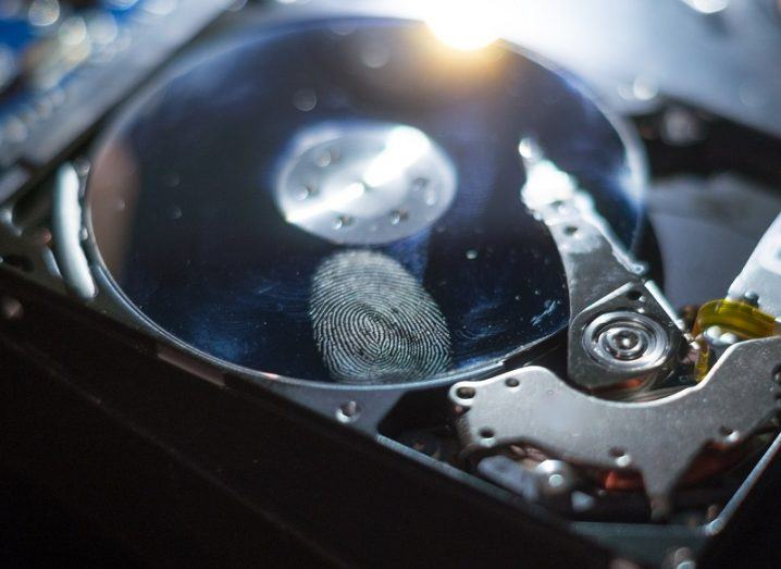Filter shot of an opened hard drive with a fingerprint on the disk.
