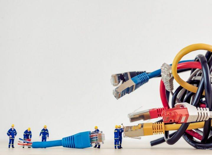 Miniature engineer figures trying to untangle a knotted number of multicoloured ethernet cables.