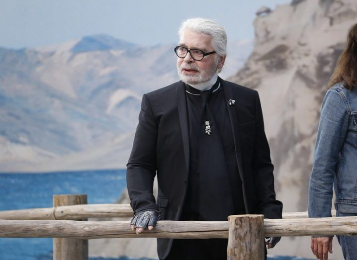Well-dressed man with white hair in black clothes overlooking a lake from a pier.