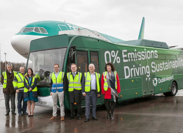 A group of people wearing high-vis vests stand in front of a green bus at Dublin Airport.