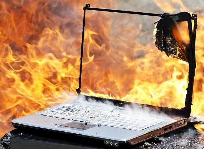 Shell of a laptop on fire and surrounded by flames.