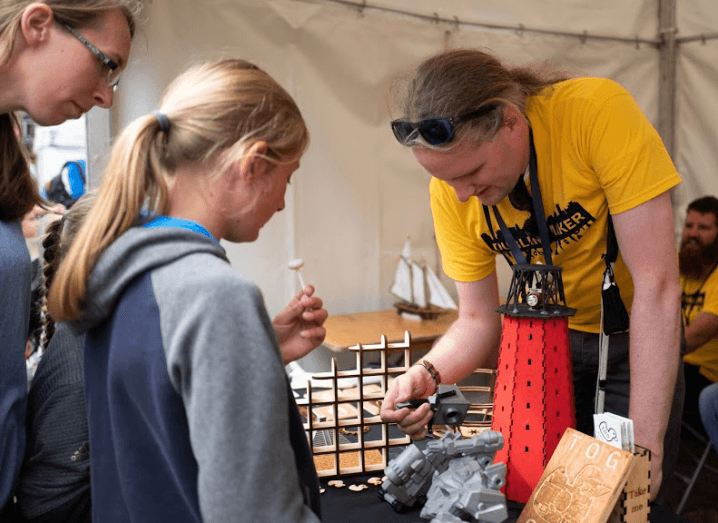 A man tinkering with wood in front of a girl and her mother at Dublin Maker 2018.