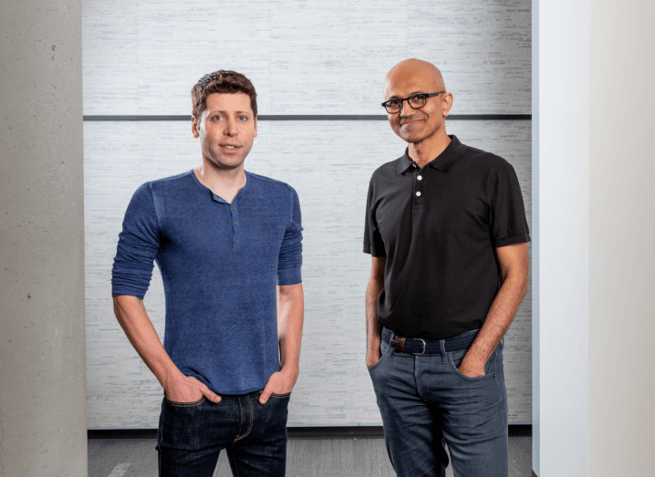 OpenAI CEO Sam Altman wears a blue long-sleeved t-shirt and jeans while standing beside Microsoft CEO Satya Nadella who is wearing a black polo and jeans.