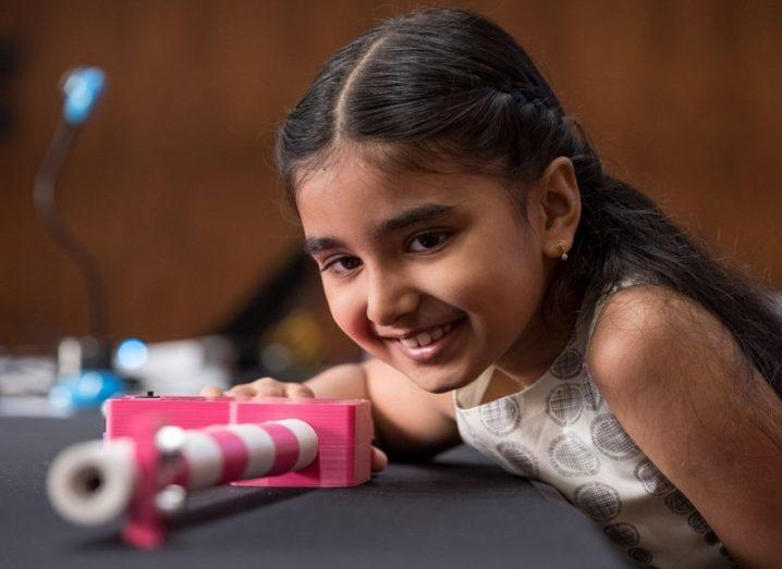 Mihika Sharma smiling while looking along the length of her pink and white Smart Stick on a table.