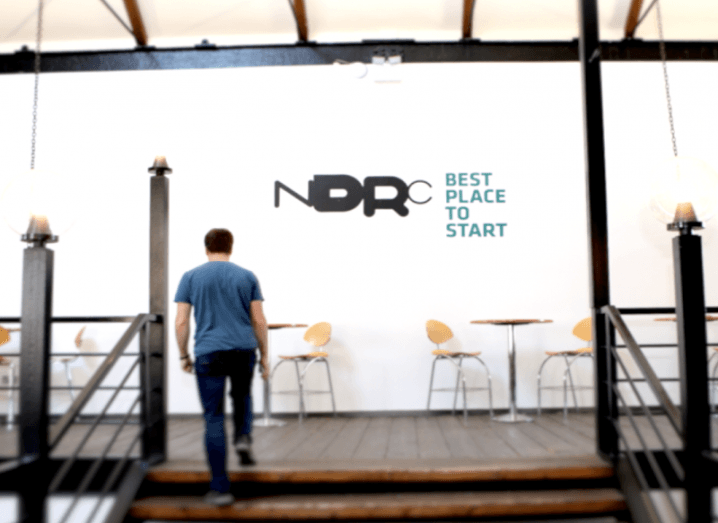 Shot of man walking up the wooden steps towards the NDRC logo on a white wall with chairs and tables beside it.