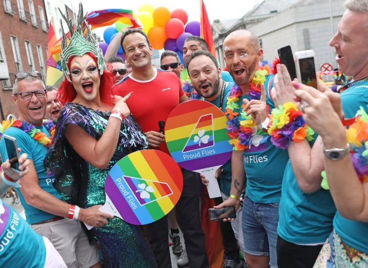 Leo Varadkar and a drag queen stand amid a group of people in Aer Lingus T-shirts and rainbow accessories.