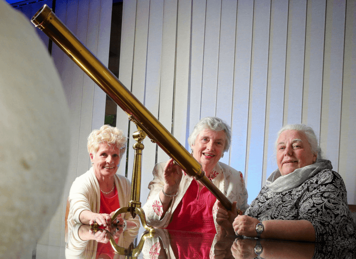 Three grey-haired women (O'Donnell, Kee and Molloy) sit at a table together with a telescope.