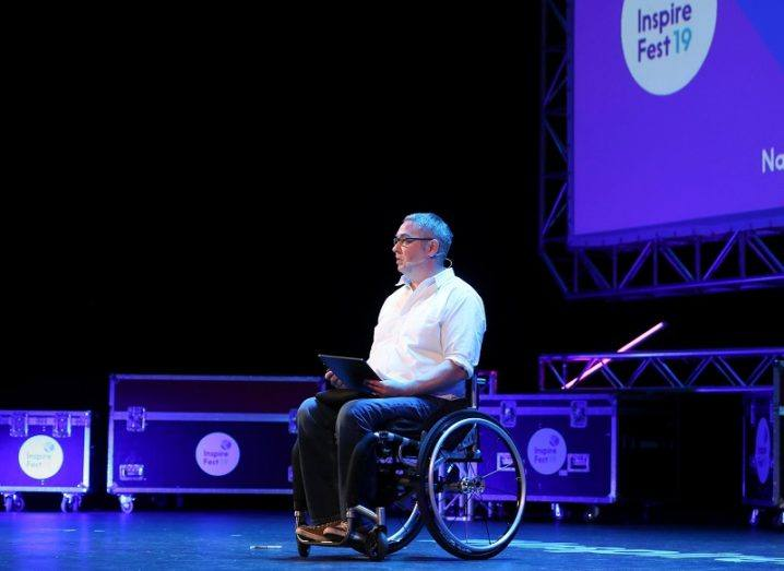 Noel Joyce in a white shirt and black trousers with equipment in the background on stage at Inspirefest 2019.