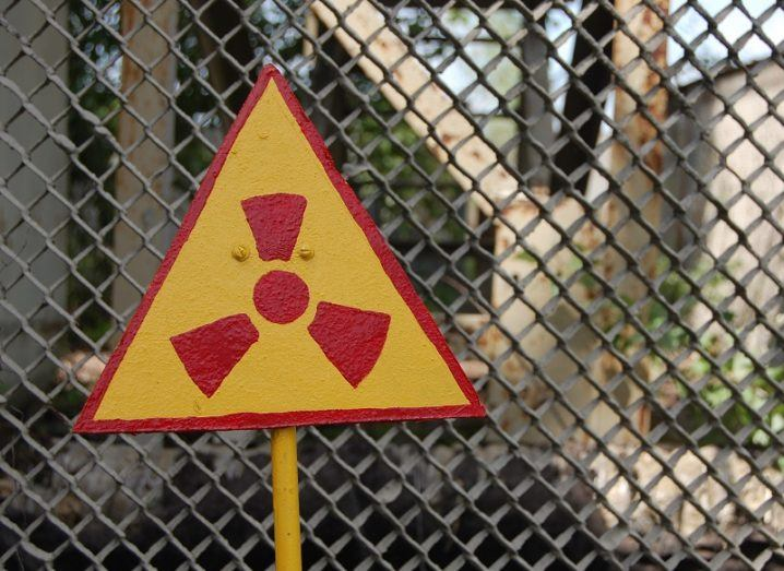 Triangular red and yellow radiation warning sign with a chain fence behind it.
