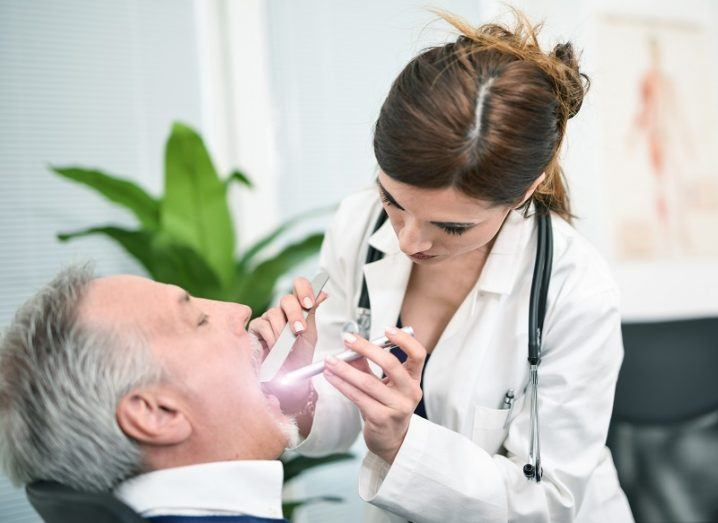 Doctor in a white coat looking down the throat of a middle-aged man with a green plant in the background.