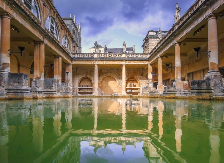 Low angled shot of green water in the square of a preserved Roman bath house with a blue sky above.
