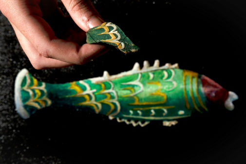 The intricate green, yellow, white and red Roman glass fish with a hand holding the UK fragment beside it.