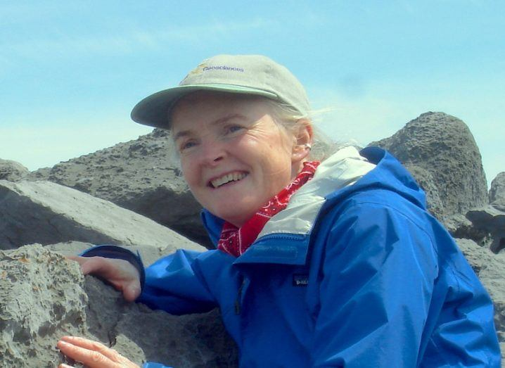 Rónadh Cox in a blue jacket and grey baseball cap smiling on a number of rocks against a blue sky.