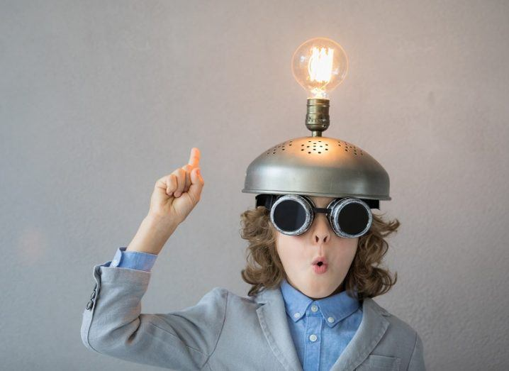 Child with curly hair standing against a grey background making a shocked expression, wearing a steel hat with a bright lightbulb.