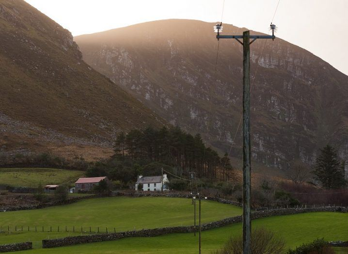 Rural Irish home on a hill surrounded by fields and mountain with an electricity pole and cables heading towards it.