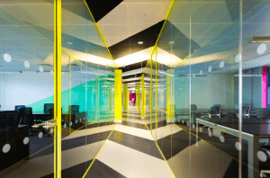 A corridor at the Huckletree offices featuring glass panels and vibrant lighting in yellow