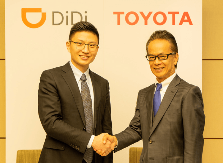 Two men wearing black suits shake hands in front of a white sign that says Didi and Toyota.