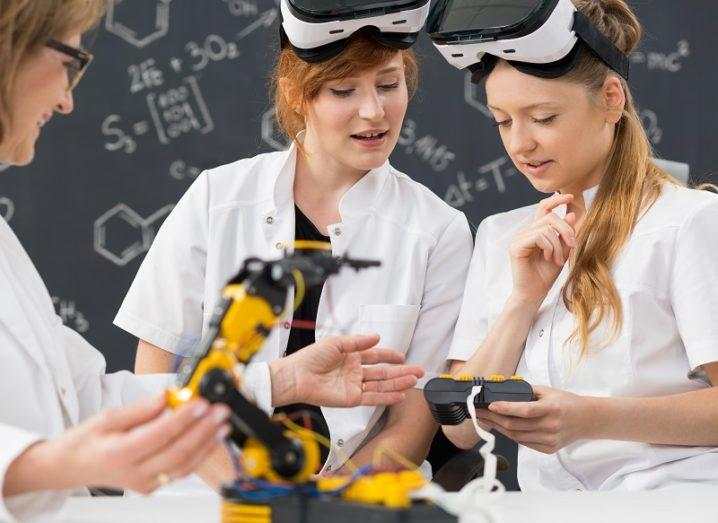 Two students in white lab coats wearing VR headsets while a lecturer tinkers with a robotic arm against a chalkboard background.