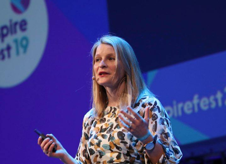 woman with long blonde hair wearing head mic and patterned dress gesturing to crowd at Inspirefest 2019 in front of purple backdrop.