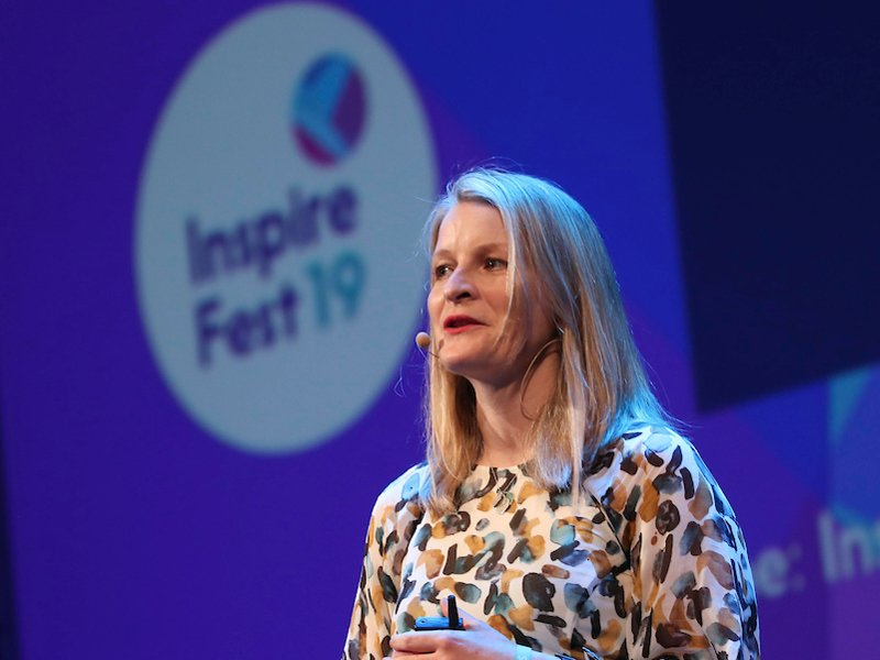 Woman with long blonde hair wearing head mic and patterned dress speaking to crowd at Inspirefest 2019 in front of purple backdrop.