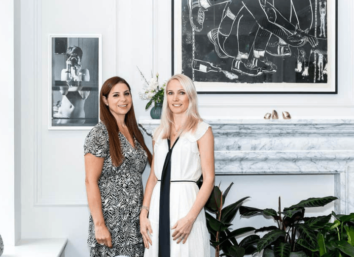 The founders of AllBright. A brown-haired woman and a blonde woman stand in front of a marble fireplace.