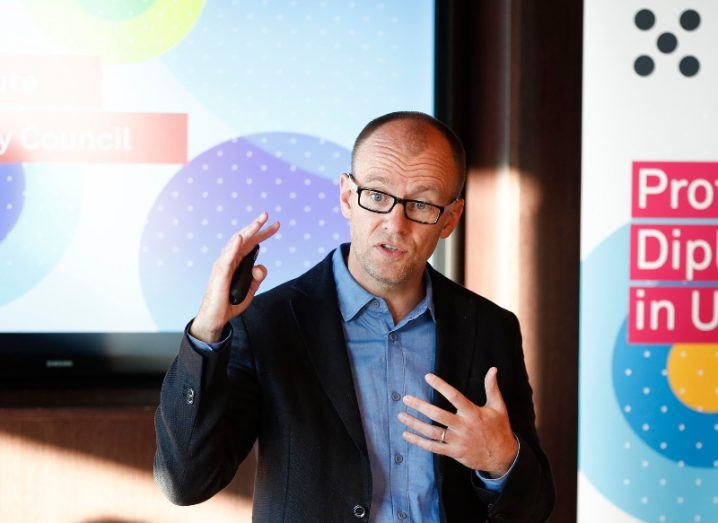 man with dark-rimmed glasses wearing blue shirt and dark blazer, gesturing as he gives presentation to crowd.