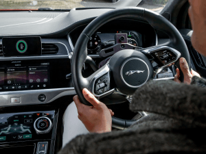 A person's hands holding the steering wheel of a Jaguar Land Rover vehicle.