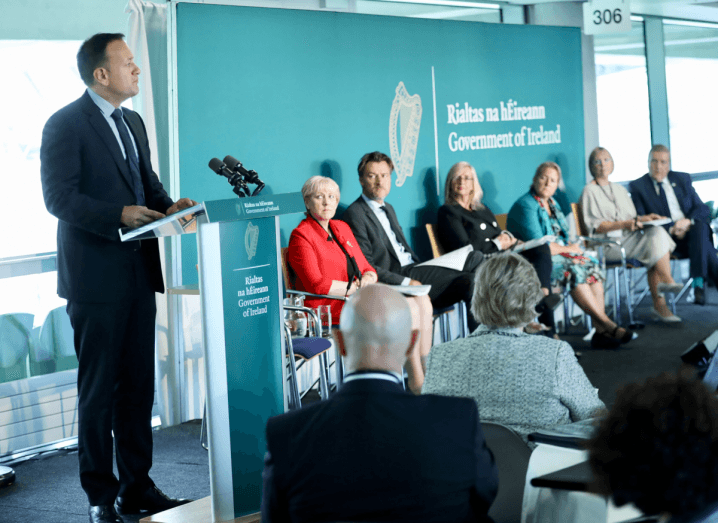 An Taoiseach Leo Varadkar stands at a podium in an Aviva Stadium conference room, while other Ministers observe him.