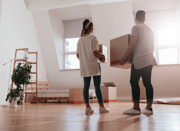 A man and woman stand in an empty new house with boxes that need to be unpacked.
