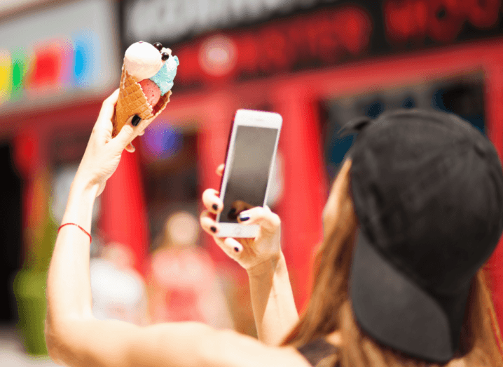 A woman holding an ice cream up in the air and taking a photograph of it with her smartphone.