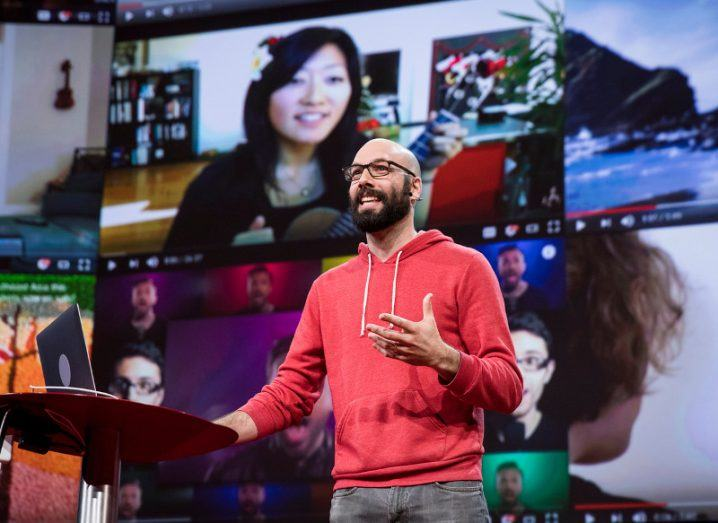 Patreon CEO Jack Conte onstage wearing a red hoodie and grey jeans.