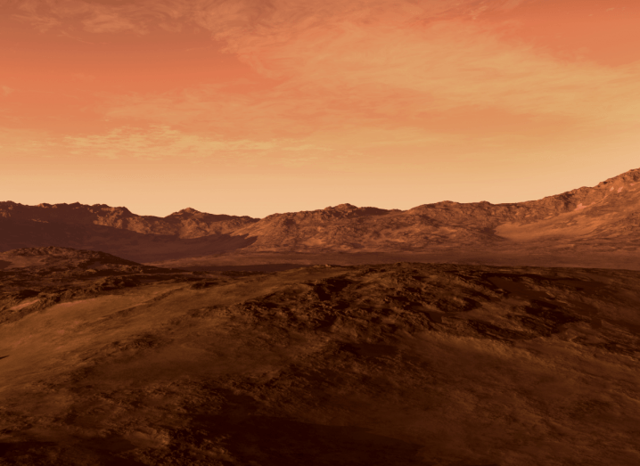 An artist's depiction of Mars as rocky, red planet with an arid landscape and mountains on the horizon.