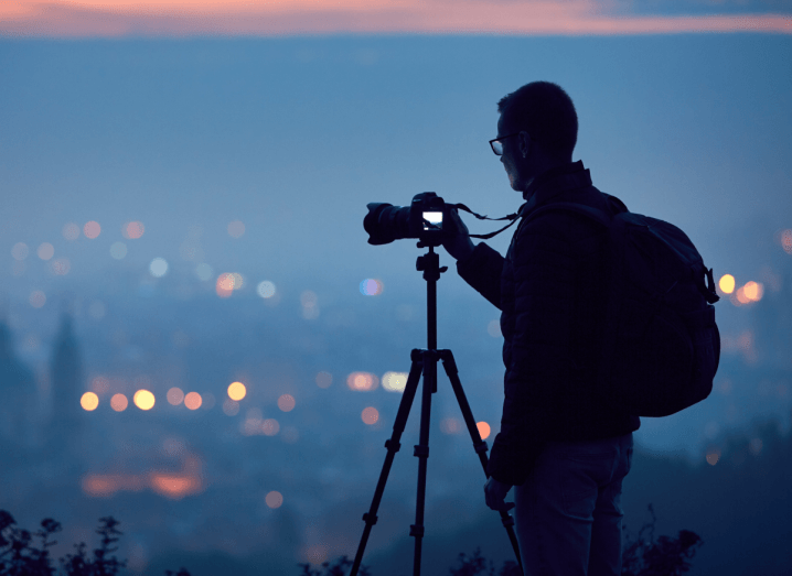 The silhouette of a photographer standing on a hill overlooking a city at dusk.