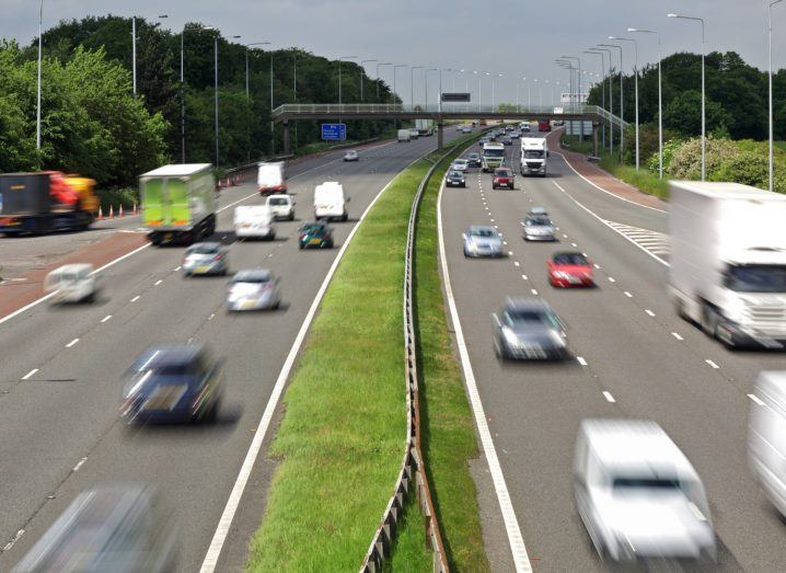 Heavy traffic moving at speed in two lanes on a motorway.