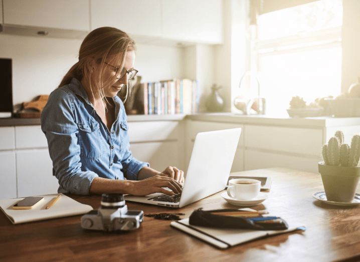 A woman works from home. She is on a laptop in her kitchen.