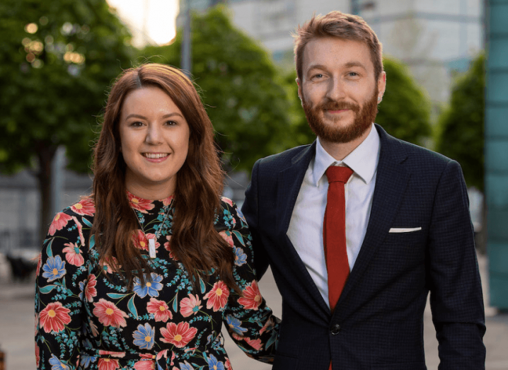 Stand co-founders Emma McQuiggan, wearing a flowery dress, and Ben Lindsay, wearing a navy suit and red tie, with their arms around each other.