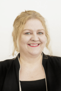 CEO of Abodoo. A middle-aged woman with blonde hair wearing a black suit in front of a white background.