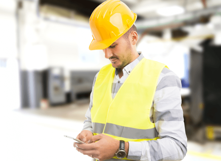 A construction worker wearing a helmet and high visibility vest using his phone in a warehouse.