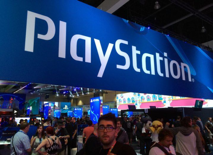 A large blue PlayStation sign hangs over a crowd gathered at the E3 event.
