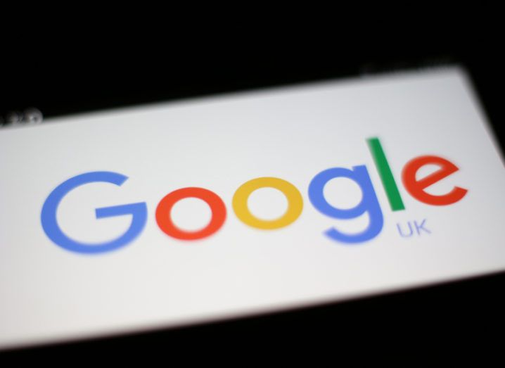 Close-up of the Google logo on a screen in a dark surrounding.