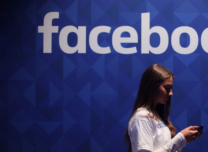 View of young woman in white blouse peering down at her phone under Facebook banner.